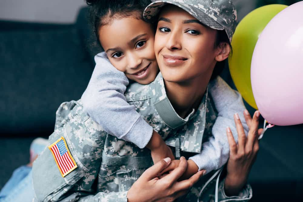 military mom with child holding baloons